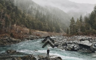 rocky river and mountain landscape with an adventurer contemplating their path forward